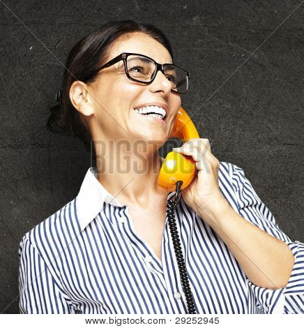 portrait of a middle aged woman talking on a vintage telephone against a grunge background