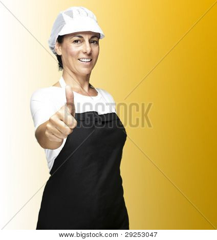 portrait of a cook wearing an apron and a hat doing an okey symbol against a yellow background