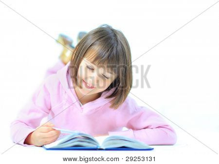 Little girl lieing on the floor and reading book