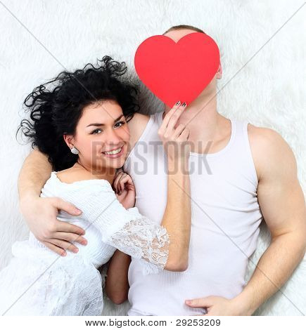 young lovely couple holding red heart together lying in a bed happy smile looking at camera valentin