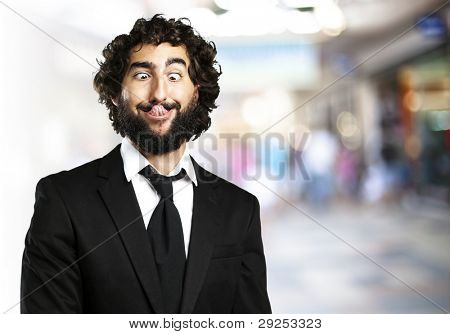 portrait of a young business man showing his tongue against a crowded place