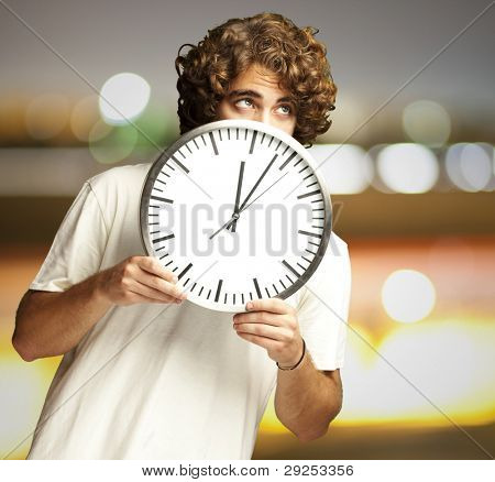 scared young man hidden behind a clock against a city by night