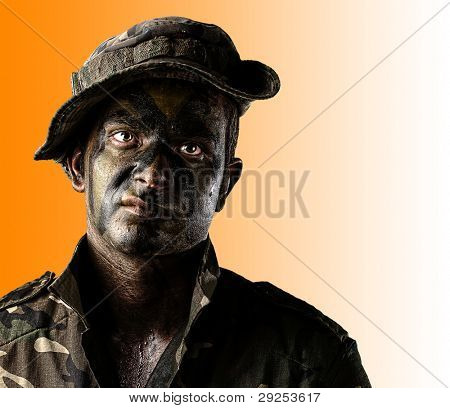portrait of a young soldier face with jungle camouflage over an orange background