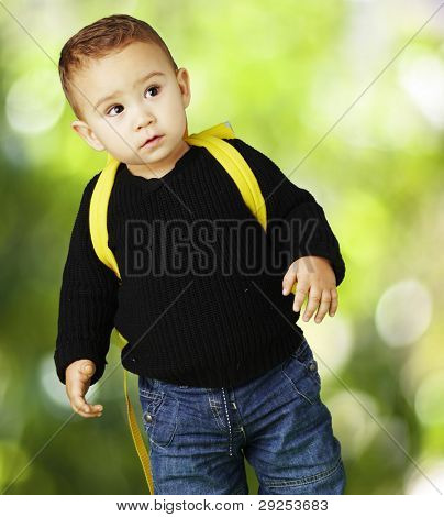 portrait of adorable kid carrying yellow backpack against a nature background