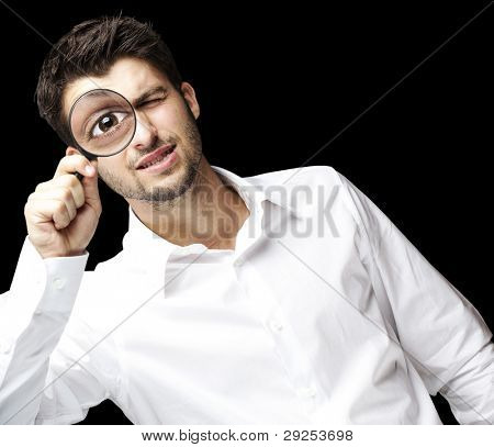 portrait of a young man looking through a magnifying glass over a black background