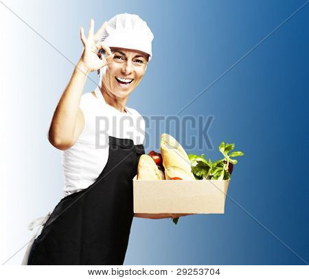 portrait of a middle aged woman carrying groceries in a box over a blue background