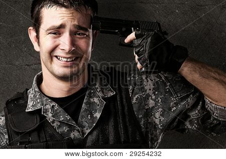 portrait of a young soldier committing suicide against a grunge wall