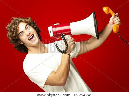 portrait of a young man shouting with a megaphone and talking on a vintage telephone over a red background