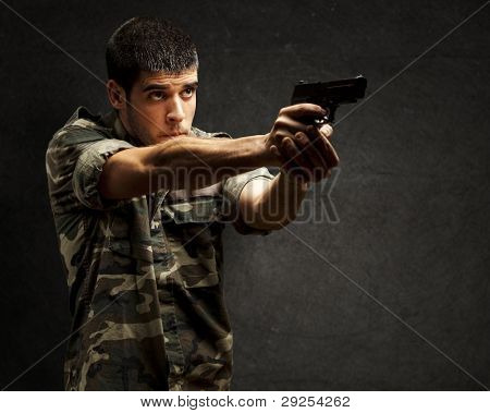 portrait of a young soldier aiming with a pistol against a grunge wall