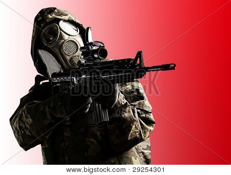 soldier with a camouflage coat, rifle and gas mask over a red background