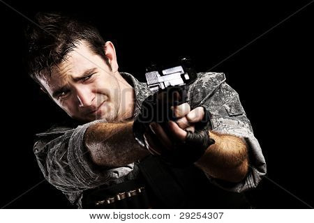 portrait of a young soldier pointing with a gun against a black background