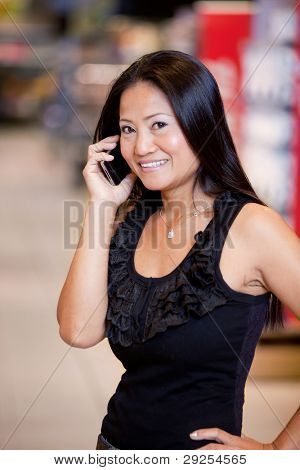 An asian woman talking on a mobile phone in a grocery store