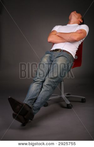 Man Relaxing On Stool On Dark Background In Studio