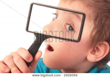 Niño mira a través de la lupa con interés