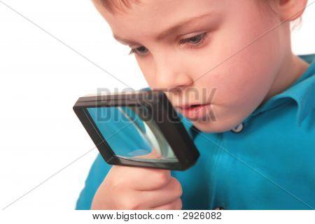 Niño mira a través de la lupa