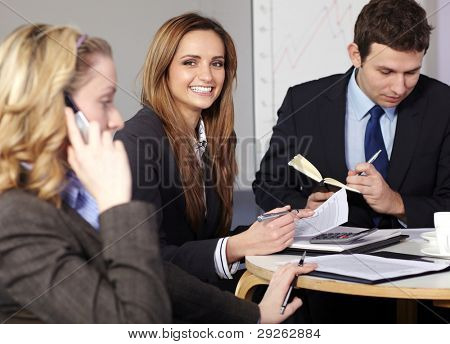 Group of 3 businesspeople sitting at table and work on paperwork