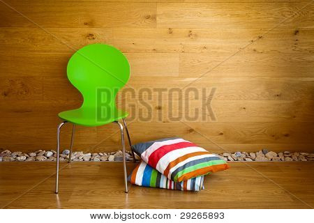 Green Chair and colorful pillows against wooden wall / Modern interior
