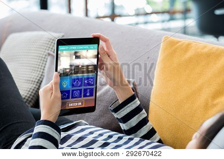 poster of Smart Home Automation Control Concpet.woman Lying Down On Sofa Using Tablet Control Device In Home.d