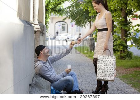 a rich young woman gives food to a beggar.
