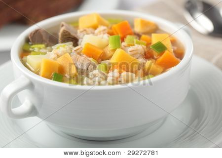 Scotch broth with lamb meat in white bowl closeup