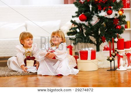 Two Happy Twins Girl Sitting With Gift Boxes Near Christmas Tree