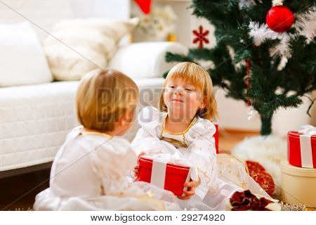 Happy Girl Sitting Near Christmas Tree And Presenting Gift To Her Sister
