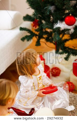 Two Girls Opening Presents Near Christmas Tree