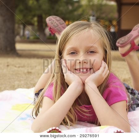 Portrait of a pretty little girl smiling happily lying on picnic blanket outdoors in park.