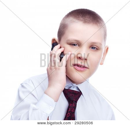 ten year old blond boy wearing a shirt and a tie, talking on the phone, isolated against white