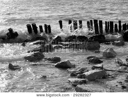 remains of wooden pier in waves
