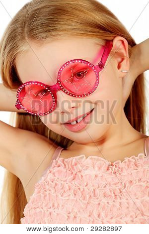 Portrait of a cute 7 years old girl in funny glasses. Isolated over white background.