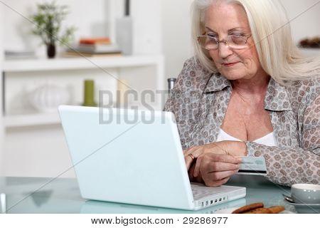 Uma senhora madura fazendo compras on-line.