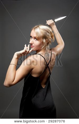 Beauty woman in evening dress with ritual knife