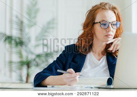 poster of Serious Experienced Female Coach Makes Records In Notepad, Focused At Screen Of Laptop Computer, Has