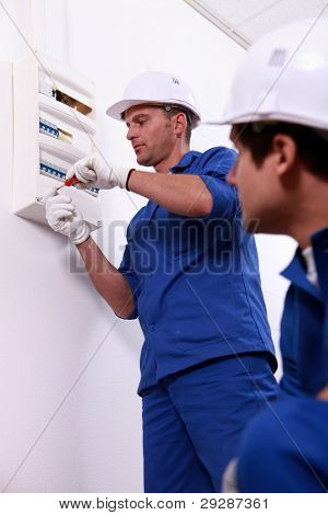 Tradesman repairing a distribution board