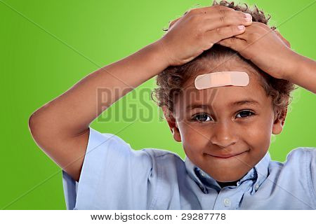 coloured little boy with plaster on his forehead against fluorescent green background