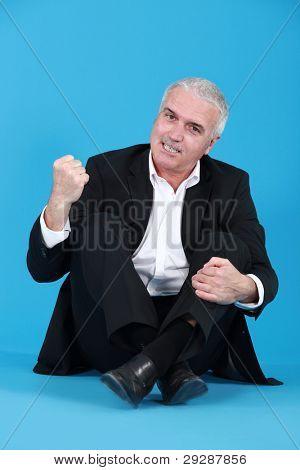 Un hombre enojado, sentado con las piernas cruzadas