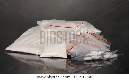 Cocaine and drugs in packages on grey background