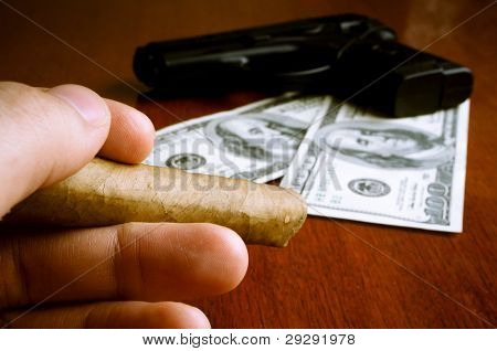 Male hand holding cigar with money and handgun in the background