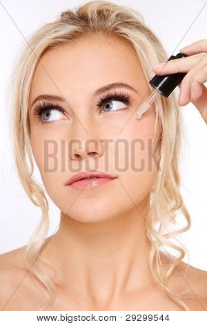 Portrait of young fresh beautiful healthy woman applying serum on her face, over white background