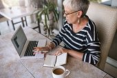 Mature Beautiful Woman Working On Her Laptop At Home. Elderly Woman Typing On Her Laptop While Readi poster