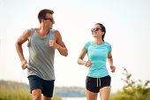 fitness, sport and lifestyle concept - happy couple in sports clothes and sunglasses running along s poster