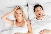 sleeping problems and people concept - unhappy woman lying in bed with snoring man poster
