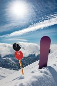 Slope Number Signs And Snowboard Standing Upright On The Edge Of Ski Slope In Snow. Sunny Winter Day poster