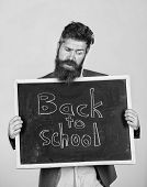 Teacher Advertises Back To Studying, Begin School Year. Teacher Or Bearded Educator Stands And Holds poster