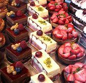 picture of french pastry  - Colorful pastries topped with fruits on display in a French patisserie - JPG