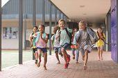Front view of happy school kids running in corridor at school poster