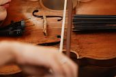 Close-up Of A Violin With A Bow. Brown Orchestra Violin. Fingers On Violin Keyboard. poster