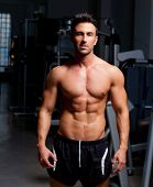 stock photo of macho man  - fitness shaped muscle man posing on dark gym - JPG