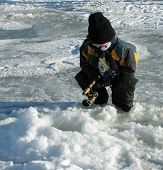 image of ice fishing  - a small boy ice fishing on an alberta lake - JPG